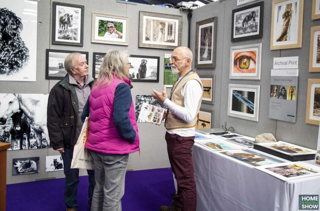 stall holder talking to customers about print media at a stand
