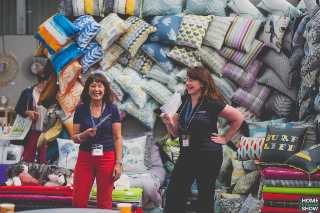 laughing women standing infront of wall of cushions