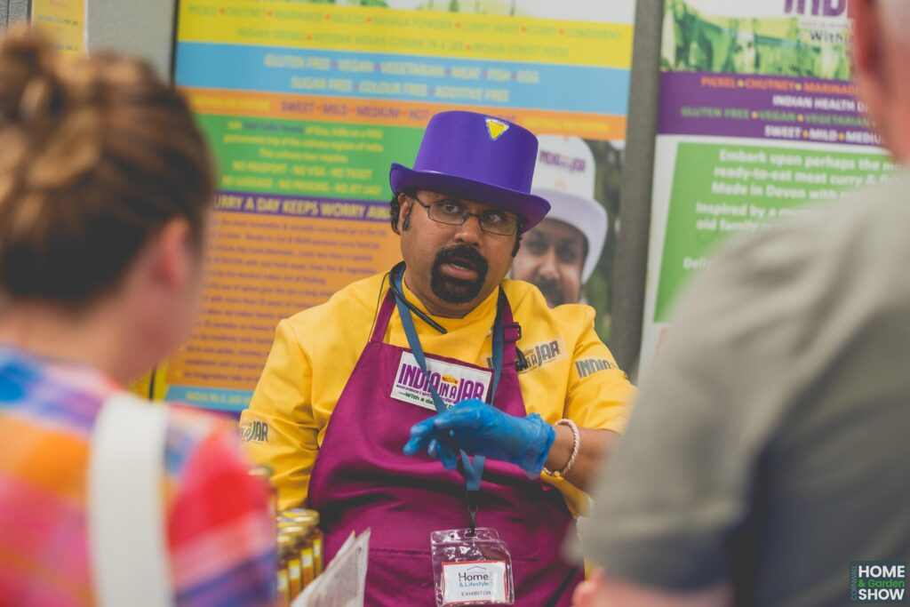 indian man wearing purple hat and glasses talking about india in a jar